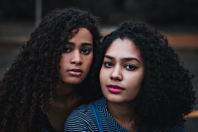 two women with curly hair standing outdoor