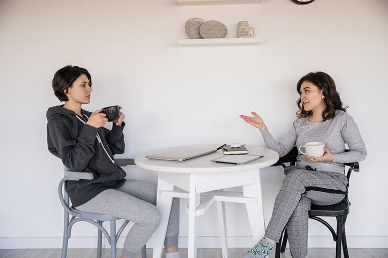women talking to each other while holding cups