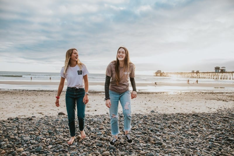 two women walking on pebbles and laughing