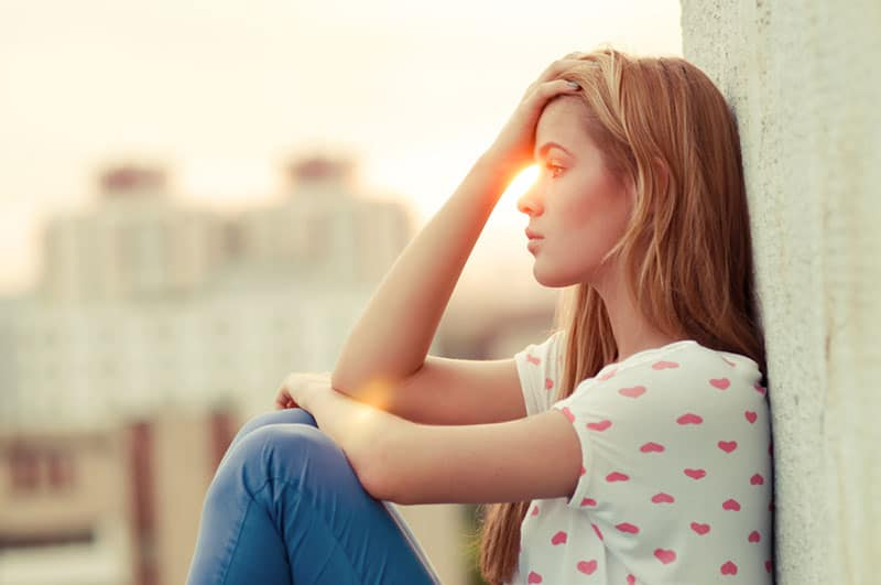 worried blond woman sitting by the wall