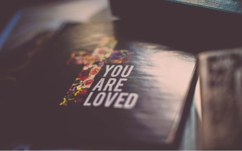 You are loved message written on a book cover near cross