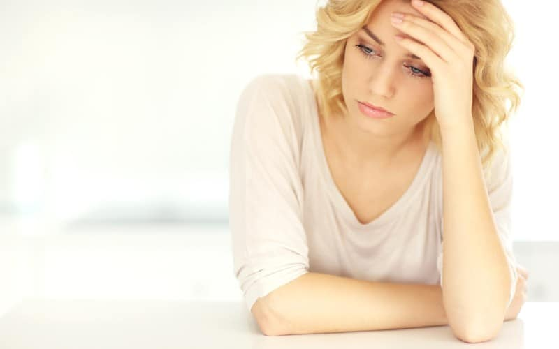 Young depressed blonde woman sitting with white background