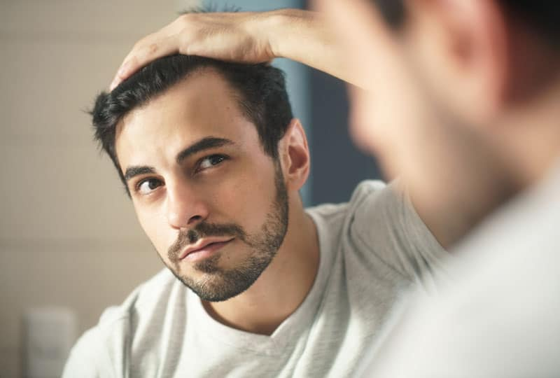 young handsome man looking at mirror