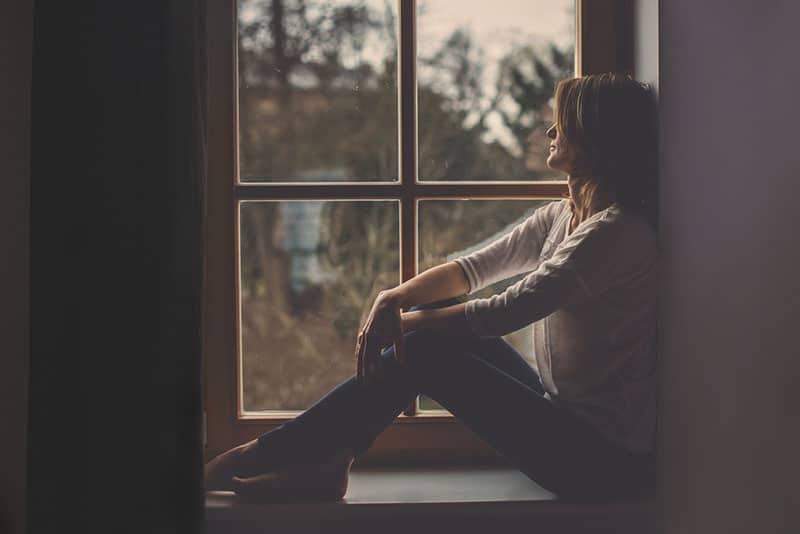 young sad woman sitting next to window