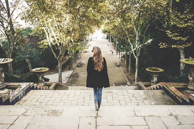 young woman in black coat walking in park