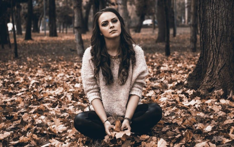 young woman siting on the ground in the forest in autumn time