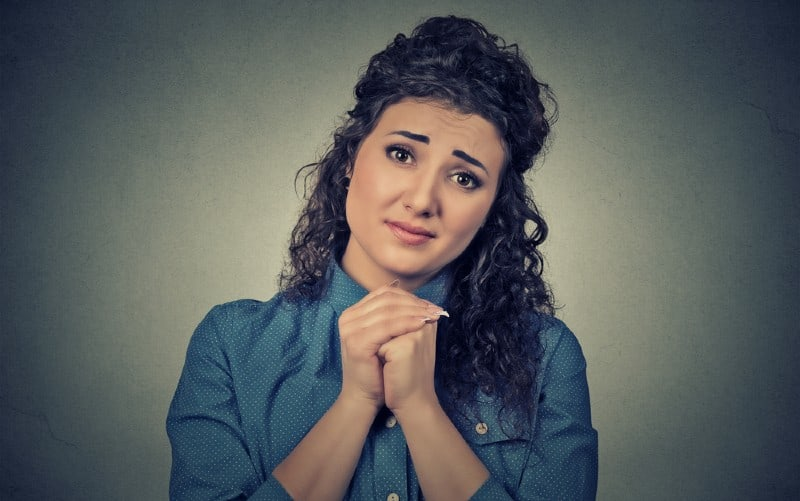 Young woman with clasped hands feeling sorry