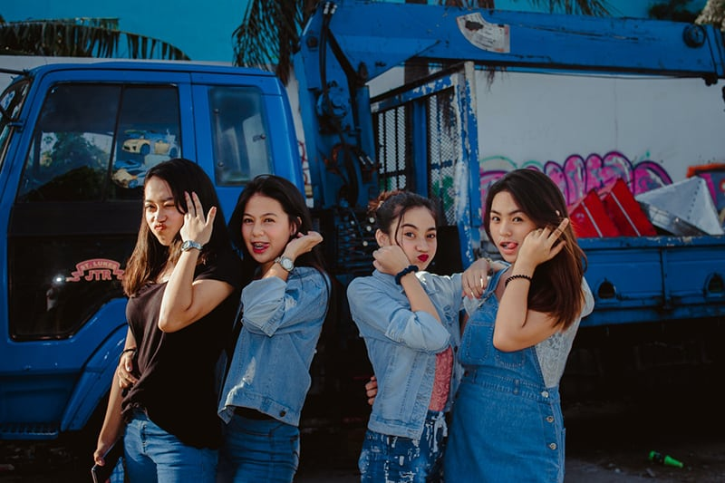 young women in casual wear standing in a front of truck