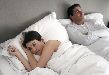 man daydreaming while lying beside his wife on bed while awake