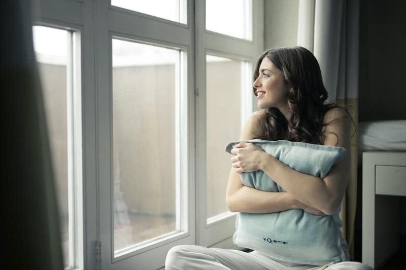 black-haired woman hugging gray pillow near glass panel window