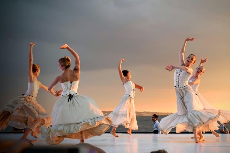 5 women in white dress dancing under gray sky during sunset