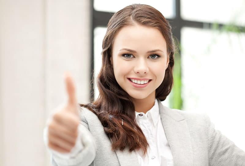 woman in office attire giving a thumbs up for approval