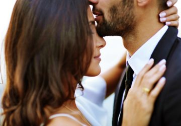 man kissing woman on her forehead outdoor