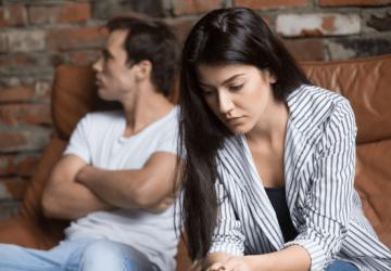 sad woman sitting on couch near man