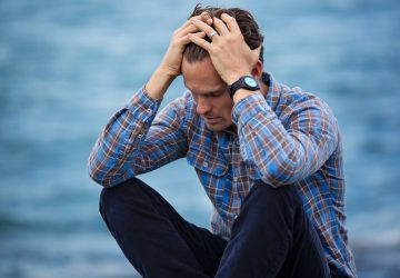 troubled man sitting near a body of water with hands on his head