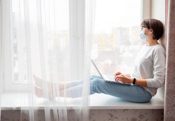 woman on self isolation wearing face mask while sitting on window pane laptop on her lap