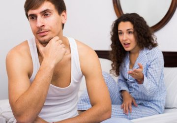 woman in pajamas nagging a man in white tank top while sitting on bed