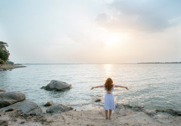 woman in white dress standing on rock looking at sea