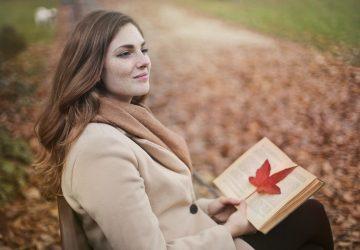 red haired woman smiling sitting on a park holding a book with a leaf in it during autumn season