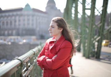 woman in red coat near river