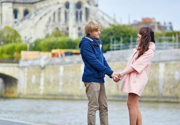 young dating couple on the Seine embankment near the Notre Dame de Paris