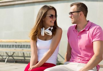 woman in white top and red pants with headphone round her neck sitting next to a guy in pink shirt sitting outside in daytime