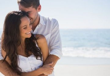 attractive couple cuddling at the beach wearing white tops