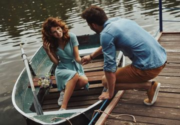 woman in a boat wearing blue dress assisted by a guy to get up by holding her hand