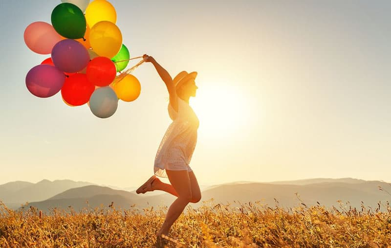 happy woman hopping in the middle of the field carrying different colored balloons