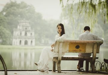 woman and man sitting on bench near water