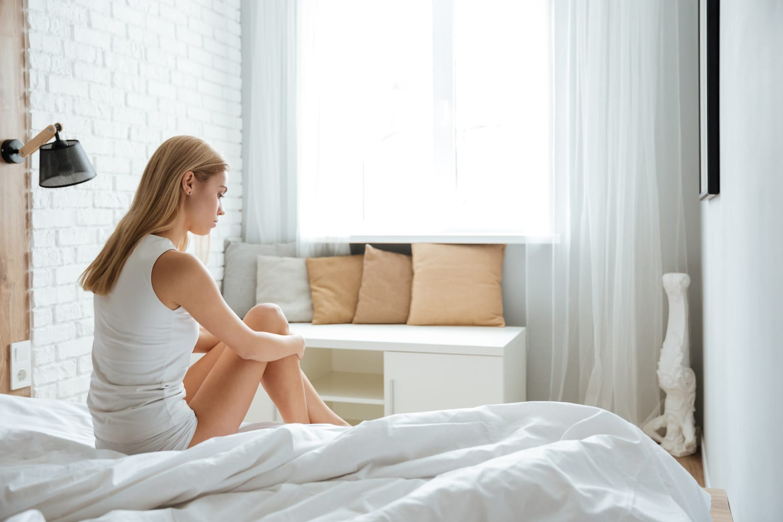 sad woman sitting on bed