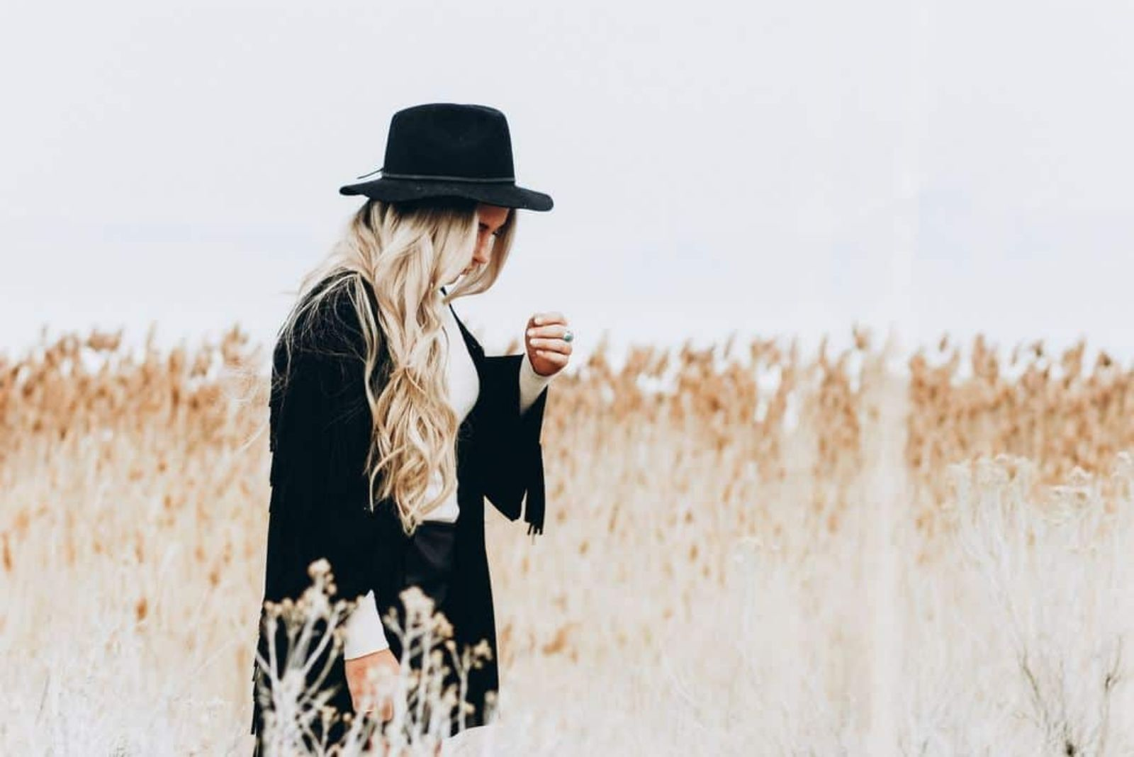 a zen of long blue hair with a black hat standing in a field