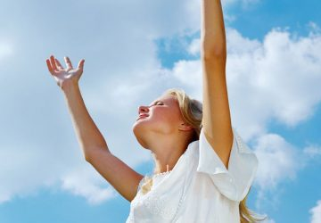 woman with arms raised smiling wearing white dress during daytime