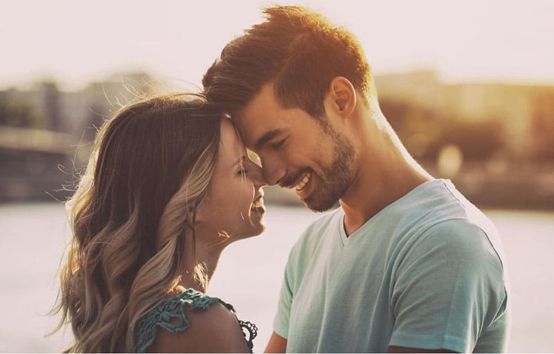 sweet couple with face close to each other near a body of of water