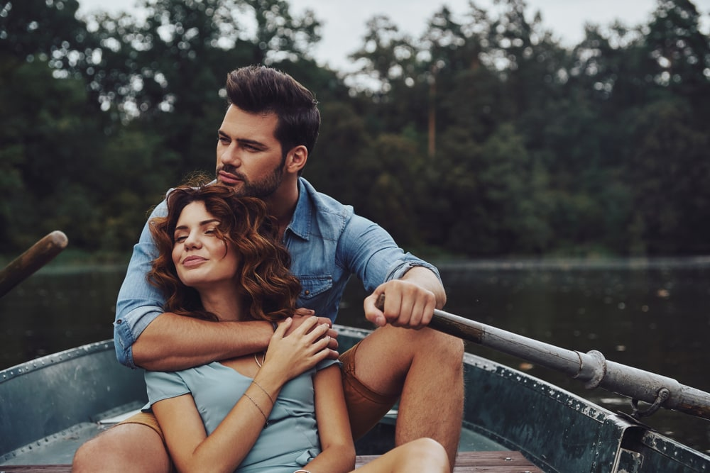 a loving couple sitting in a boat and enjoying themselves