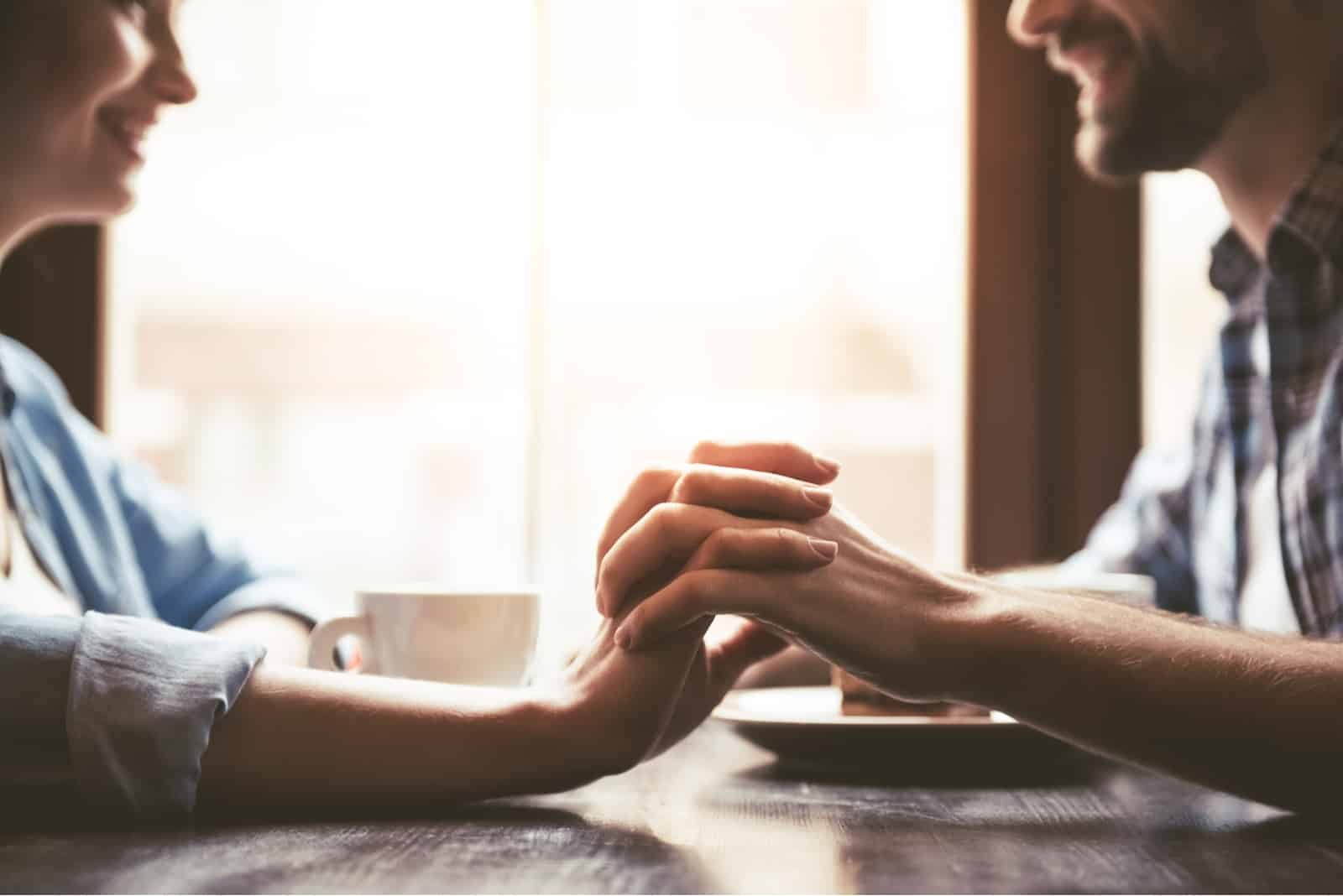 a man and a woman sit and hold hands