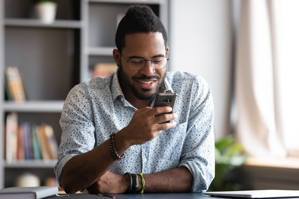 a smiling black man sits in the office and writes an sms