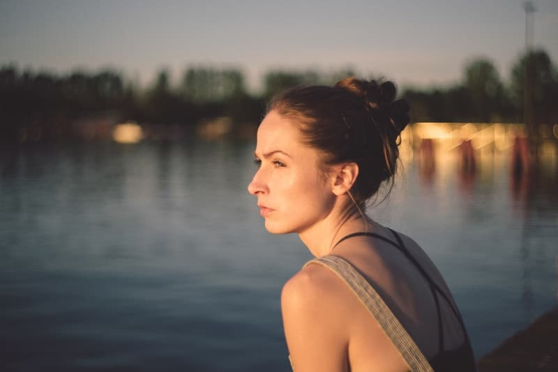 adult woman in a blur city sitting near the lake
