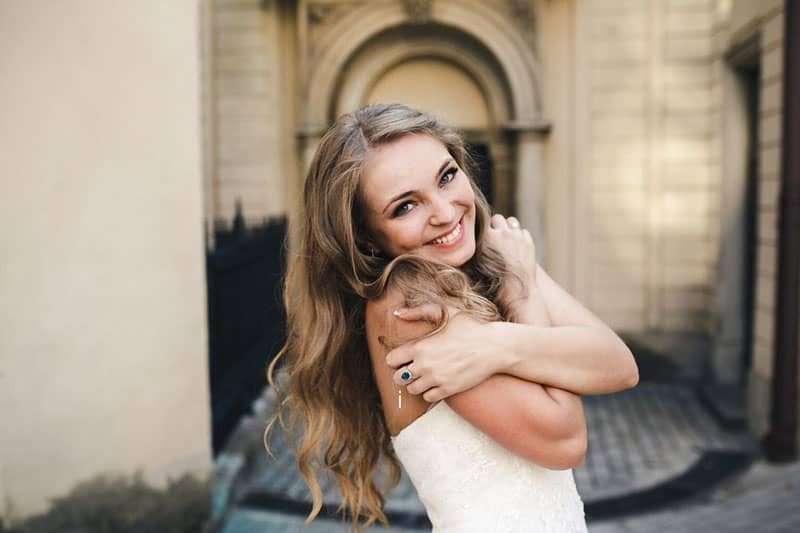 beautiful woman embracing herself smiling wearing white dress