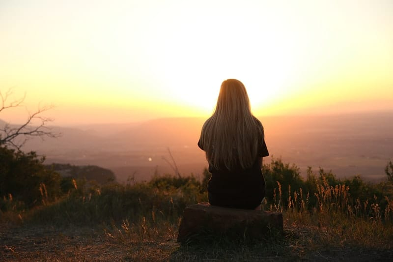 behind of a woman sitting on rock on top of a mountain looking at the sunset