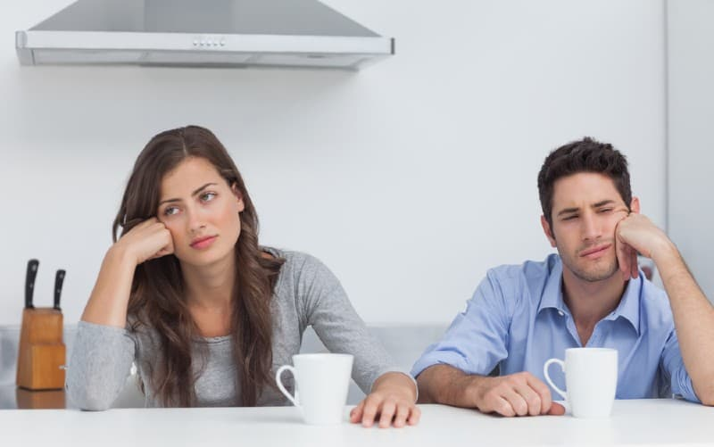 Bored couple sitting at table next to each other with white mugs in front of them
