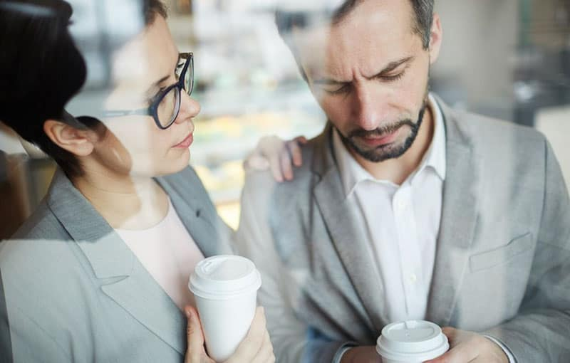 business woman trying to comfort a sad man while on coffee break