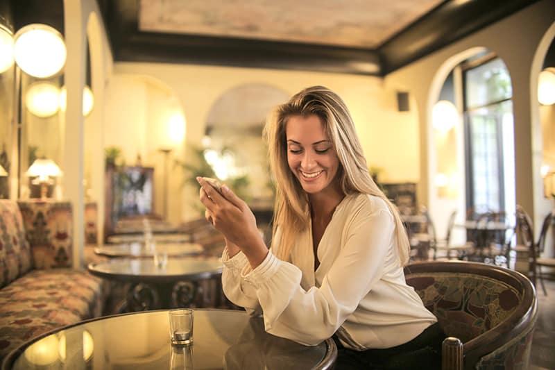 cheerful female having drink in elegant bar while using smartphone