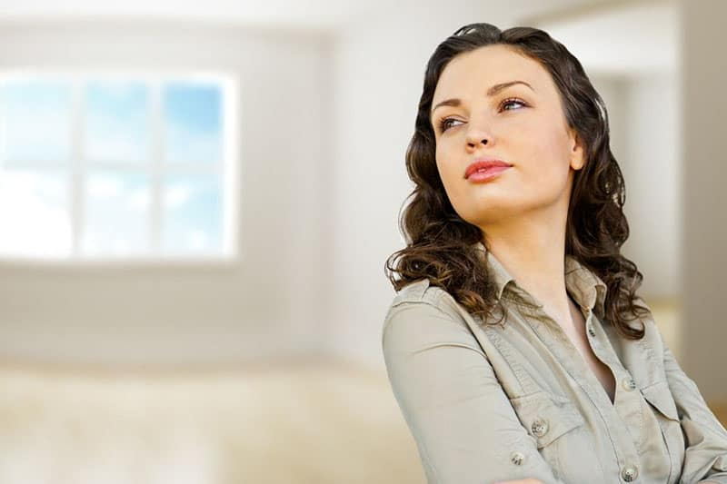 confident woman in gray top inside an empty room