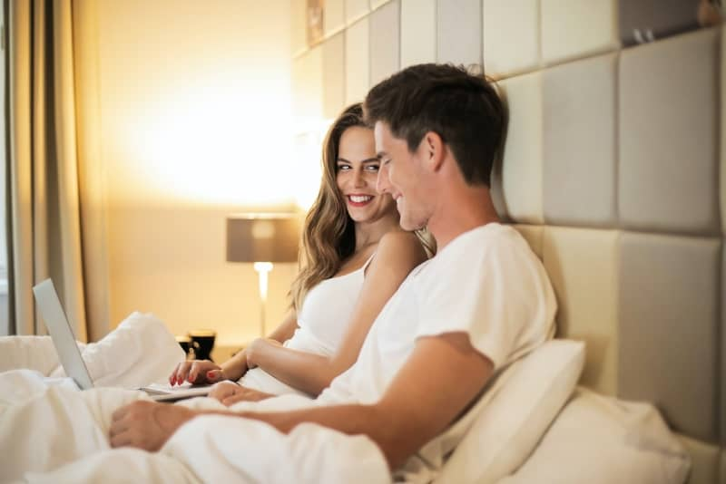 woman and man browsing laptop while sitting on bed