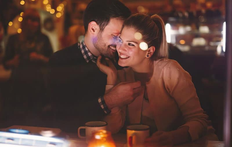 couple date night in a pub man whispering the smiling woman