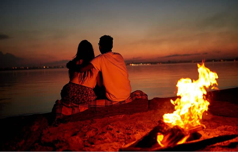 couple dating by the beach with a bonfire behind them