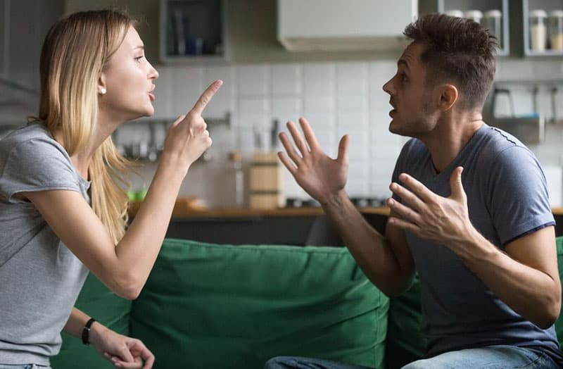 couple fighting over couch near the kitchen