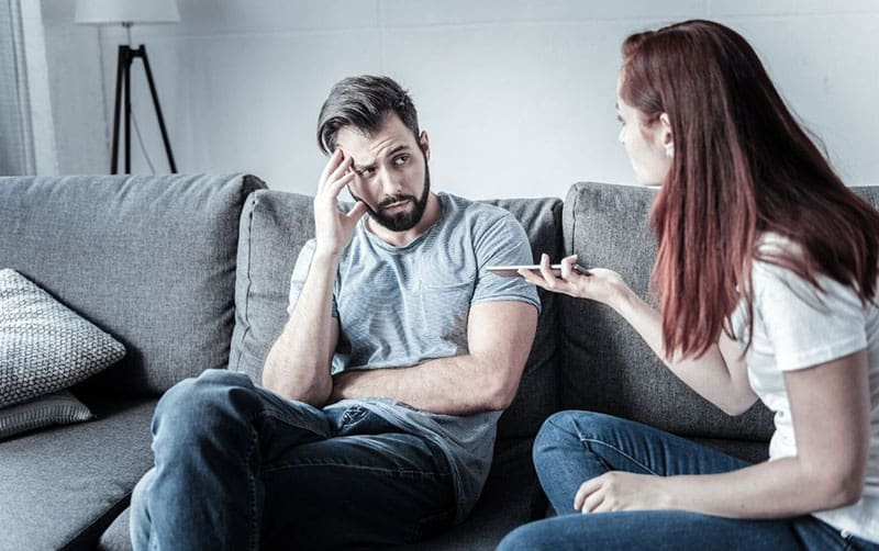 couple fighting while sitting on gray sofa