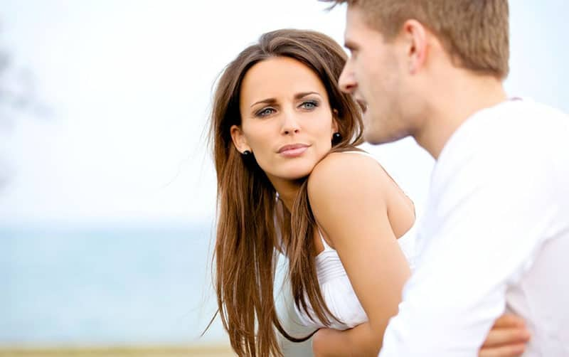 couple having a conversation wearing white top woman looking at the man talking